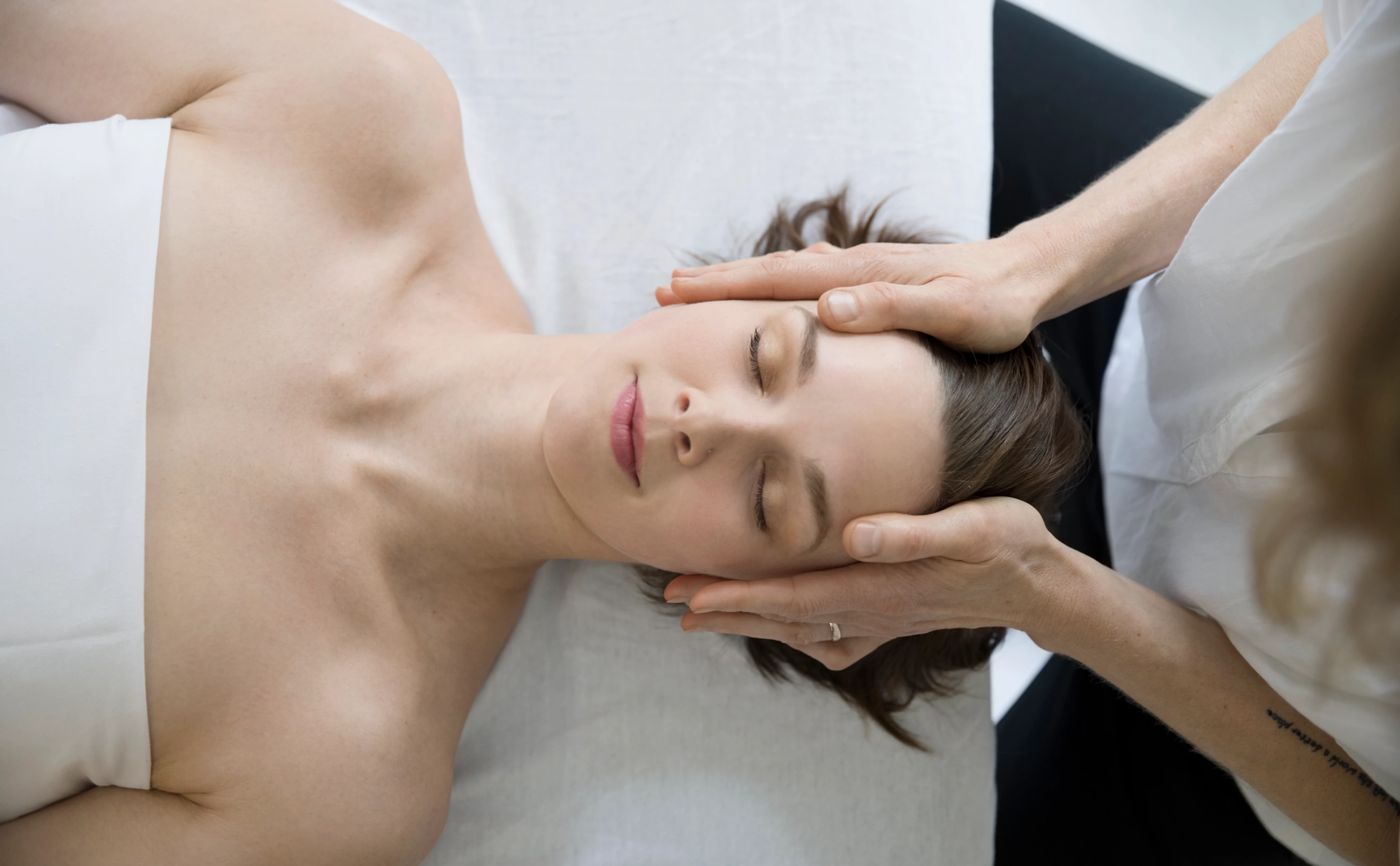 Woman laying on a spa bed getting a facial treatment